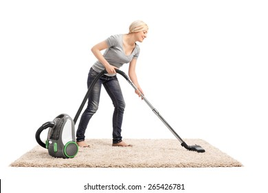 Full length portrait of a woman vacuuming a beige colored carpet with a vacuum cleaner isolated on white background