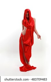 full length portrait of a woman wearing a red silk draped gown. creative dancing poses isolated on a white background.