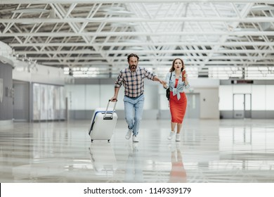 Full length portrait of worried male and woman running with baggage indoor. They late for flight
