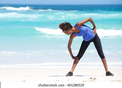 Full length portrait of young african woman exercising on the beach