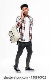 Full length portrait of a young african male student dressed in plaid shirt with a backpack talking on mobile phone and looking away isolated over white background