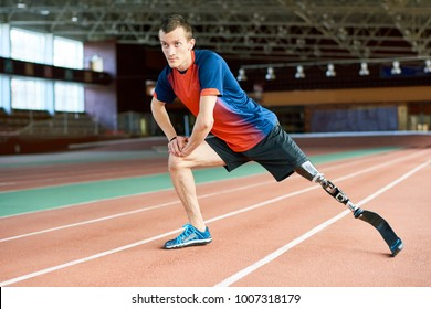 Full length portrait of young amputee sportsman  warming up before running practice in modern gym stretching legs on track, copy space