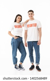 Full length portrait of a young attractive couple standing isolated over white background, wearing volunteer t-shirts