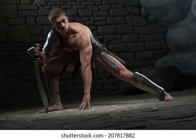 Full length portrait of young attractive warrior gladiator with muscular body holding sword on dark background. Concept of masculine power, strength