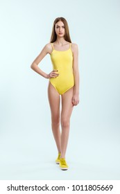 Full length portrait of young beautiful girl in yellow swimsuit and sneakers. Beach, rest, sport, relax concept