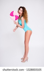 full length portrait of young beautiful woman in swimsuit posing with giant lollipop over gray background