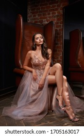 Full length portrait of young beautiful elegant woman sitting and posing at leather chair in dark interior. Pretty female model in luxury evening dress. Lady with perfect makeup and brunette wavy hair