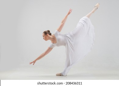 Full length portrait of young and beautiful modern style ballet dancer taking classical ballet poses, lifting leg up isolated on white background, studio shot
