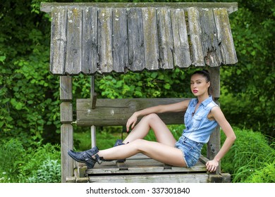 Full length portrait of young beautiful brunette woman in blue jeans short sitting on a wooden old well