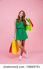 Full length portrait of young beautiful readhead curly woman in green dress, holding colourful shopping bags, isolated over pink background