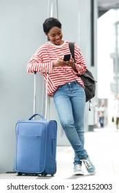 Full length portrait of young black woman standing with suitcase and looking at mobile phone while waiting at the airport