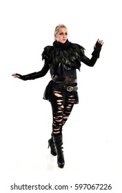 full length portrait of a young blonde lady wearing a futuristic torn leather outfit. isolated against a white background.