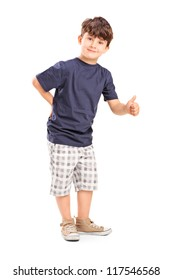 Full length portrait of a young boy giving a thumb up isolated on white background