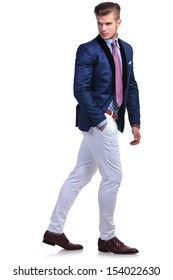 full length portrait of a young business man walking while looking back, away from the camera, and holding a hand in his pocket. on a white background