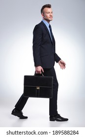 full length portrait of a young business man walking to the side and looking away from the camera while holding a suitcase in his hand. on a light gray studio background
