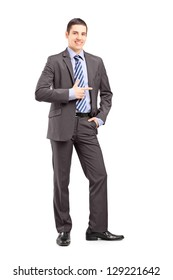 Full length portrait of a young businessman standing and pointing isolated on white background