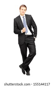 Full length portrait of a young businessman in formalwear leaning against wall isolated on white background