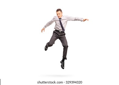 Full length portrait of a young businessman jumping in the air and looking down isolated on white background