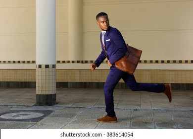 Full length portrait of young businessman running and looking over shoulder