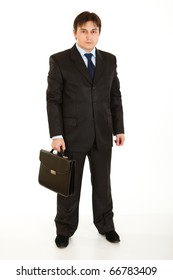 Full length portrait of young businessman holding briefcase in hand isolated on white