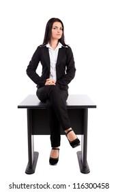Full length portrait of a young businesswoman sitting on table isolated on white background