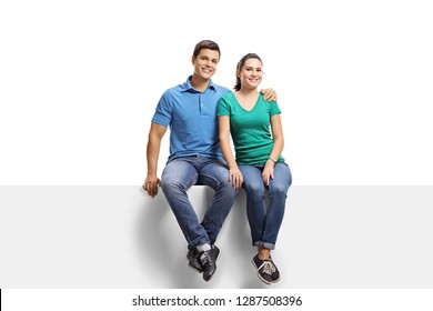 Full length portrait of a young casual couple sitting on a panel and smiling at the camera isolated on white background