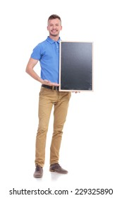 full length portrait of a young casual man presenting a blank blackboard and smiling for the camera. isolated on a white background