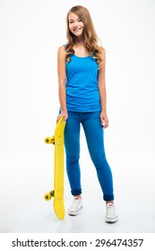 Full length portrait of a young casual woman standing with skateboard isolated on a white background. Looking at camera