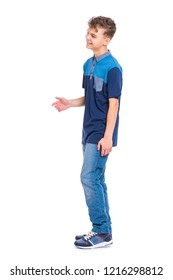 Full length portrait of young caucasian teen boy isolated on white background. Funny teenager walking. Handsome active child stretching his right hand for greeting, looking away and smiling.