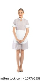 Full length portrait of young chambermaid in tidy uniform on white background