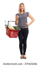 Full length portrait of a young cheerful woman carrying a shopping basket full of groceries isolated on white background