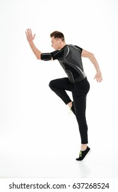 Full length portrait of a young concentrated sportsman in earphones jumping isolated over white background