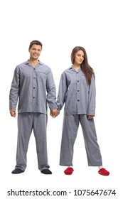 Full length portrait of a young couple in pajamas holding hands isolated on white background