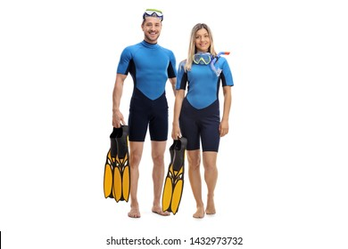 Full length portrait of a young couple in wetsuits, holding diving flippers and smiling at the camera isolated on white background