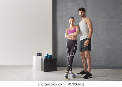Full length portrait of a young couple standing together at the gym.
