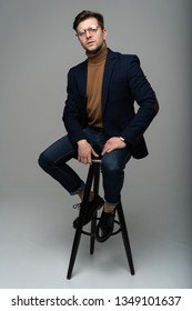 full length portrait of a young fashion man sitting on a chair and looking into the camera on a gray background