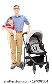 Full length portrait of a young father holding his baby daughter and pushing a baby stroller isolated on white background
