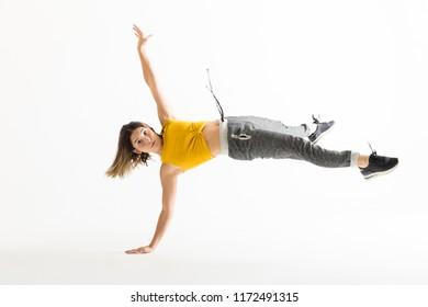 Full length portrait of young female break dancer doing handstand over white background