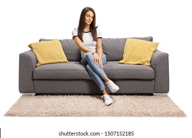 Full length portrait of a young female sitting on couch with legs crossed isolated on white background