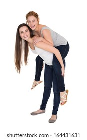 Full length portrait of a young female piggybacking friend over white background