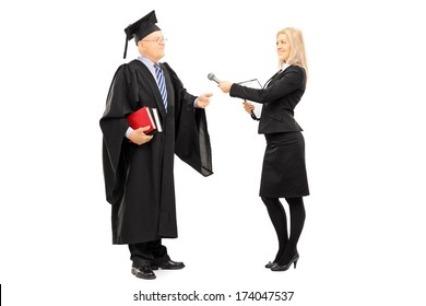 Full length portrait of young female interviewing mature man in graduation gown isolated on white background