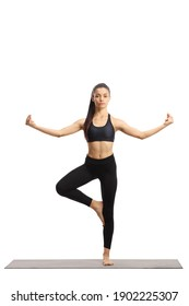 Full length portrait of a young female in a yoga pose on an exercise mat isolated on white background