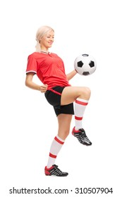 Full length portrait of a young female soccer player in a red jersey and black shorts juggling a football isolated on white background