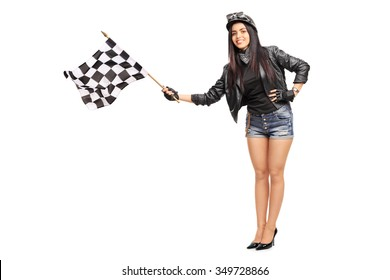 Full length portrait of a young female biker waving a checkered race flag isolated on white background