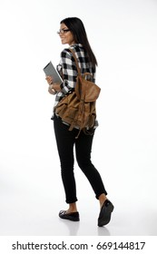 Full length portrait of young female student in glasses and  plaid holding tablet computer and backpack walking away from camera. isolated on white background