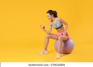 Full length portrait young fitness sporty woman in sportswear working out isolated on yellow background. Workout sport motivation lifestyle concept. Sit on fit ball doing exercise with dumbbell