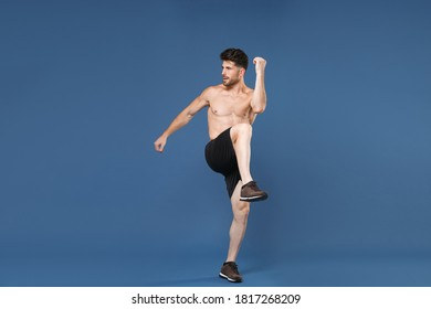 Full length portrait of young fitness sporty strong man bare-chested muscular sportsman isolated on blue background. Workout sport motivation lifestyle concept. Doing stretching exercising for legs