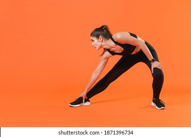 Full length portrait of young fitness sporty woman in black sportswear posing training working out doing stretching exercising for legs looking aside isolated on orange color wall background studio