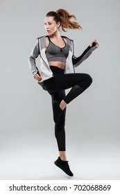 Full length portrait of a young fitness woman in sportswear posing and jumping isolated over gray background
