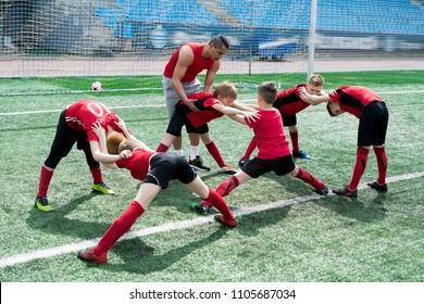Full length portrait of  young football coach helping group of boys doing stretching exercises during warm up before practice in outdoor stadium, copy space